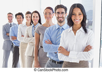 Business team with folded arms smiling at work