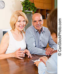 Smiling mature couple of pensioners talking with employee at...