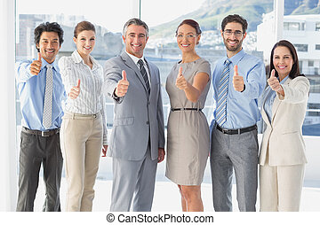 Employees giving a thumbs up at work