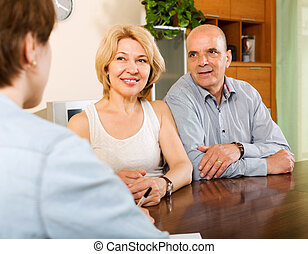 Mature couple with insurance agent - Positive mature couple...
