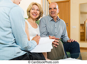 mature couple discussing details of private insurance with...