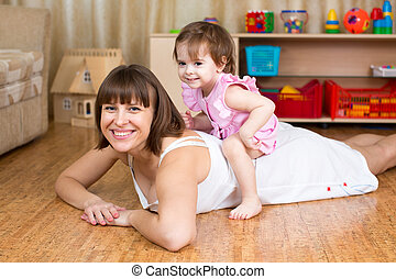 happy mother having fun with her daughter on back