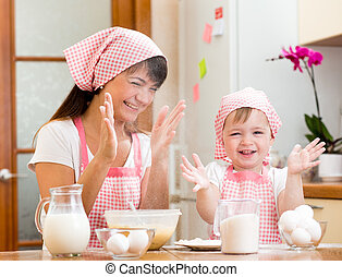 Mother and kid have fun preparing cookies at kitchen