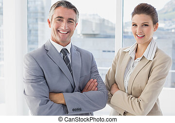 Business man and woman smiling while in the office