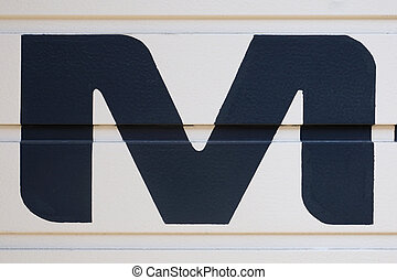 letter M - black uppercase letter M painted on garage door