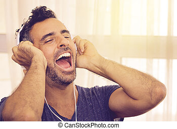 Exuberant man listening to his music - Exuberant handsome...