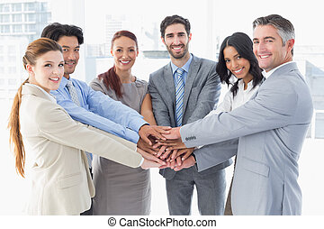 Business team stacking their hands together while smiling