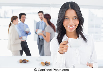 Smiling businesswoman with a drink at work