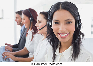 Employee's typing on their computers using headsets