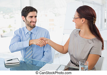 Business colleagues shaking hands in a meeting