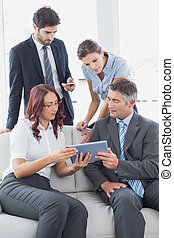 Business team looking at a tablet in work