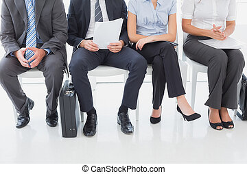 Business people sitting in a row in an office