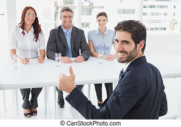 Smiling businessman giving thumbs up with colleagues