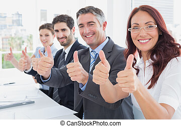 Business team all giving thumbs up at work