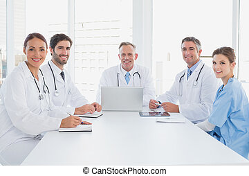 Doctors smiling at the camera as they all sit