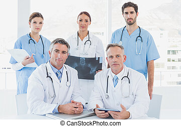 Doctors looking serious at camera as they work