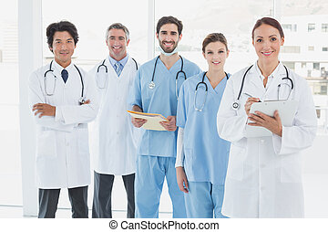 Smiling doctors all standing together and looking at the...