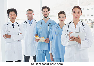 Serious doctors all standing together and looking at the...