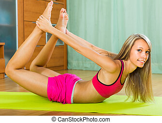 Female doing yoga at home - Happy slender young woman doing...