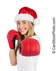 Festive blonde punching with boxing gloves on white...