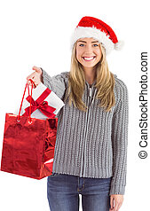 Festive blonde holding christmas gift and bag on white...