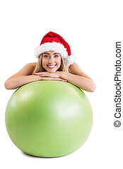 Festive fit blonde posing with exercise ball on white...