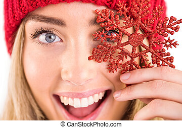 Happy blonde holding red snowflake on white background
