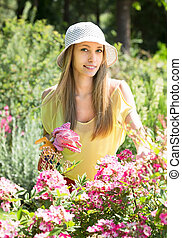 gardener walking near flowering shrubs - Female gardener...
