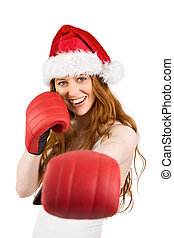 Festive redhead punching with boxing gloves on white...