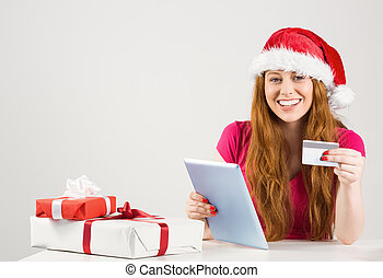Festive redhead shopping online with tablet on white...