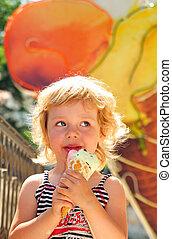 girl enjoys an ice-cream - little girl outdoors eating huge...