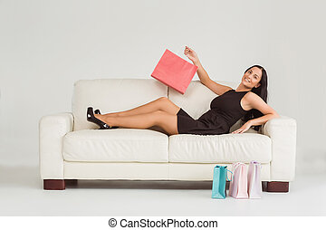 Woman sitting with shopping bags on white background