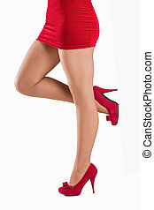 Woman standing with leg raised on white background