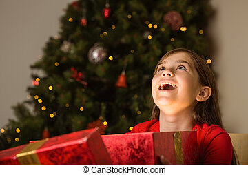 Little girl opening a magical christmas gift at home in the...