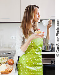Woman in apron drinking tea with cake