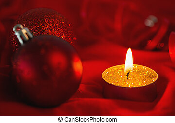 Golden tea light candle with christmas decorations on red...