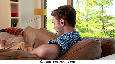 Handsome young man relaxing on his couch listening to music...