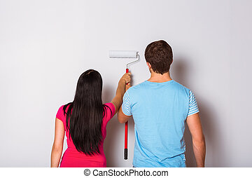 Young couple painting with roller