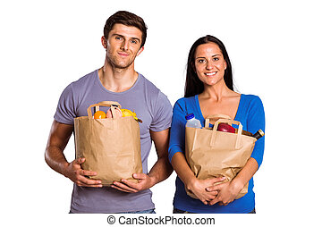 Young couple holding grocery bags on white background