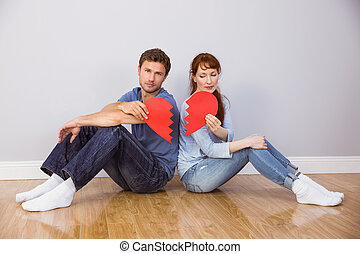 Couple holding a broken heart at home