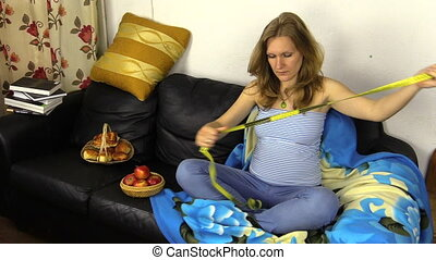 woman measure her tummy - Pregnant woman sit on sofa and...