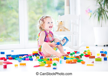 Adorable laughing toddler girl playing with colorful blocks