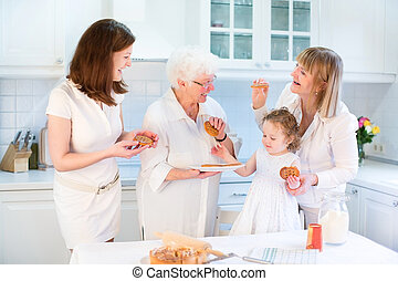 Four generations of women having fun together baking an apple pi