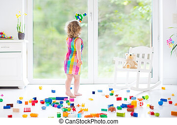 Cute laughing toddler girl playing with colorful blocks,...