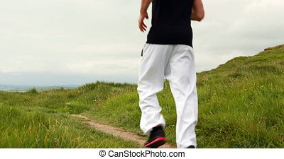 Fit man jogging through sand dunes by the coast