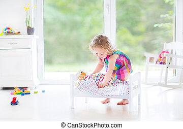 Girl playing with teddy bear - Happy beautiful curly toddler...
