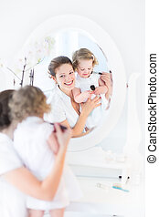 Young beautiful woman applying make up and cosmetics - Young...