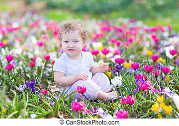Funny laughing baby playing with first spring flowers