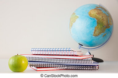 Stack on notepads on table with a globe behind them