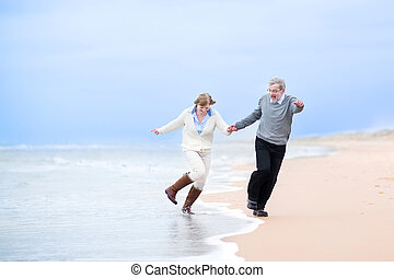 Happy middle aged couple running on a beach holding hands